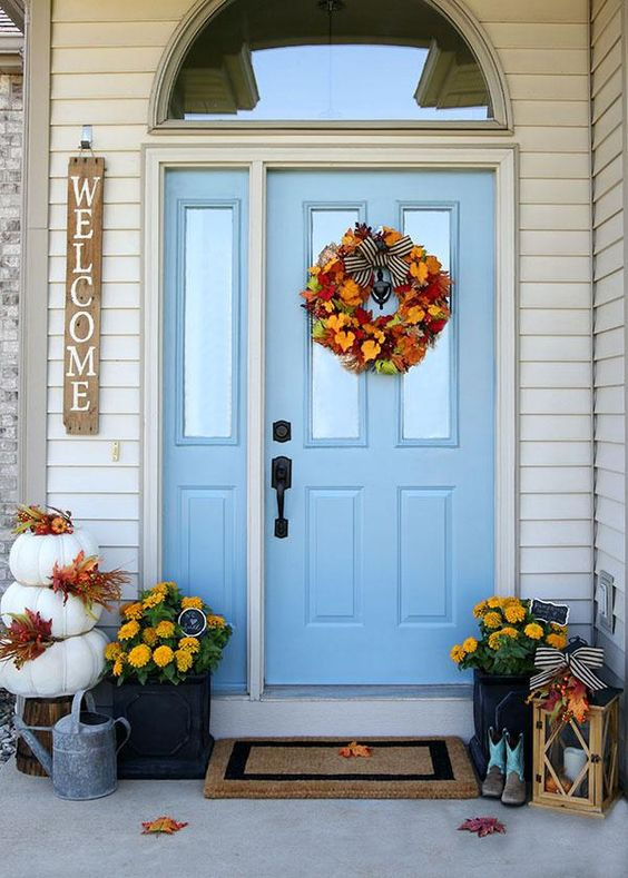 a bright Thanksgiving porch with yellow blooms potted, candle lanterns, a stack of pumpkins and a faux leaf wreath