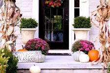 a bright and chic fall porch with corn husks, pink blooms in pots, natural pumpkins and a fall wreath