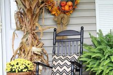 a bright and simple fall porch with a husk bundle, potted blooms, cabbage and ferns, pumpkins and a fall leaf wreath