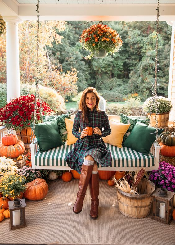 a bright and welcoming Thanksgiving porch with bold fall blooms in wooden baskets, candle lanterns, pumpkins and corn husks and fall-colored pillows