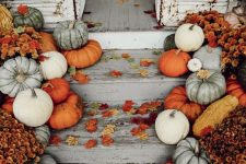 a bright fall porch with natural pumpkins in various colors, fall leaves and blooms is rustic and very welcoming