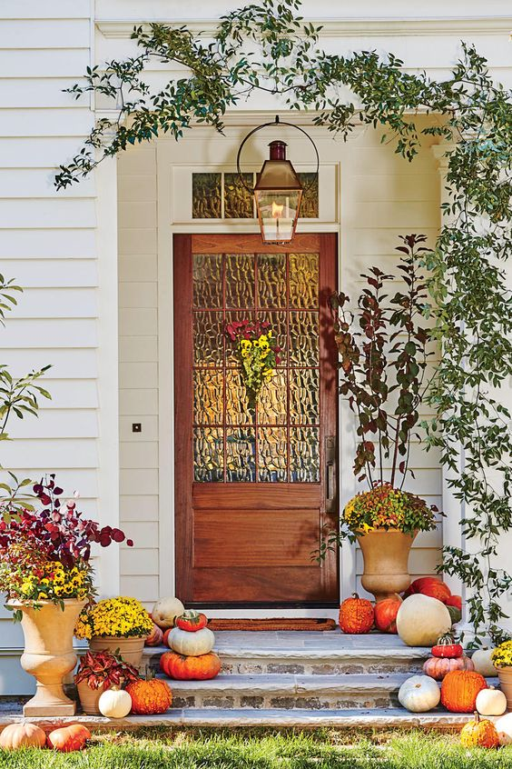a bright fall porch with natural pumpkins on the steps, bright fall leaves in urns and a candle lantern over the porch