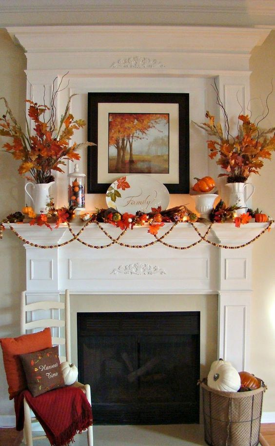 a bright rustic mantel with a wooden bead garland, bright faux leaves, pumpkins, a refined plate and artwork, bright leaves in vases