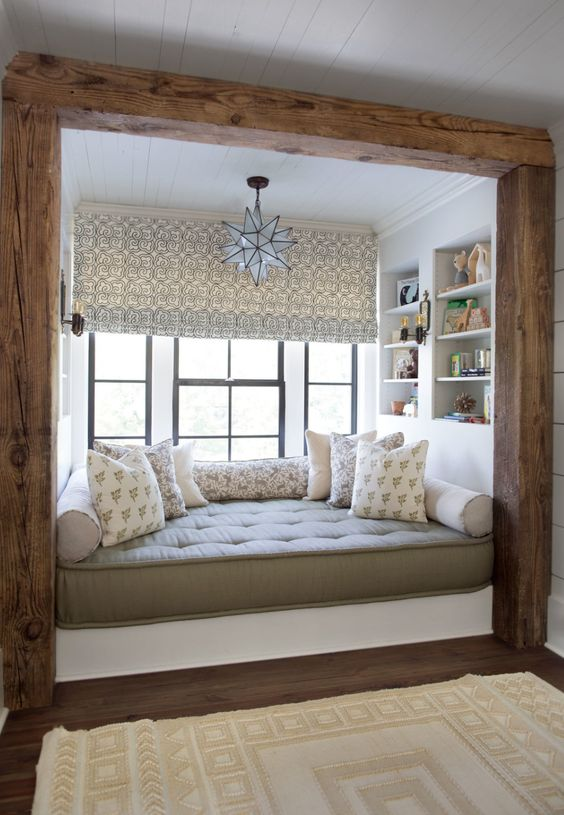 a cabin chic windowsill reading nook with a large upholstered daybed, some printed pillows and built in bookshelves