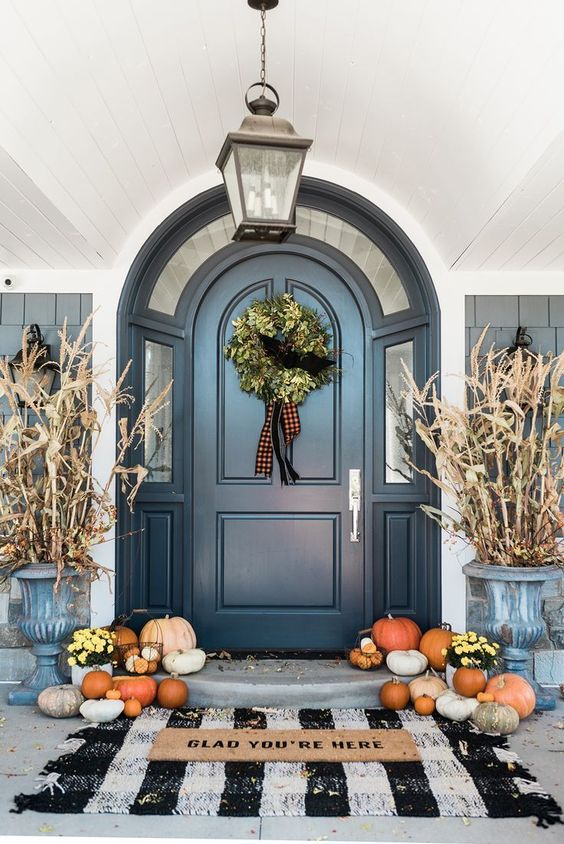 a chic Thanksgiving porch with corn husks in vintage urns, natural pumpkins and blooms in pots and a greenery wreath