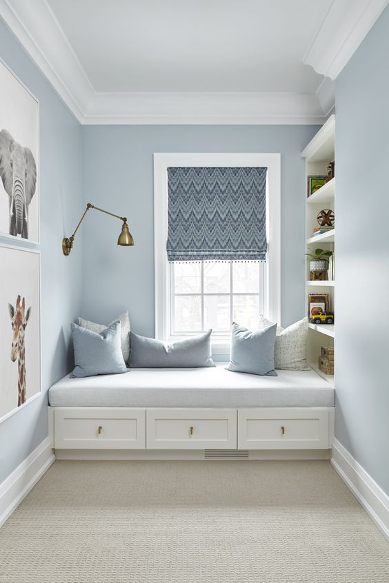 a coastal windowsill reading nook with an upholstered bench, drawers and bookshelves on one side of it