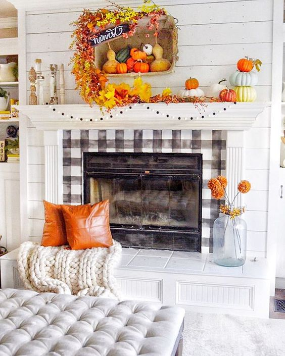 a colorful Thanksgiving mantel with bright stacked pumpkins, a pompom garland, bright faux leaves, bright faux pumpkins and gourds