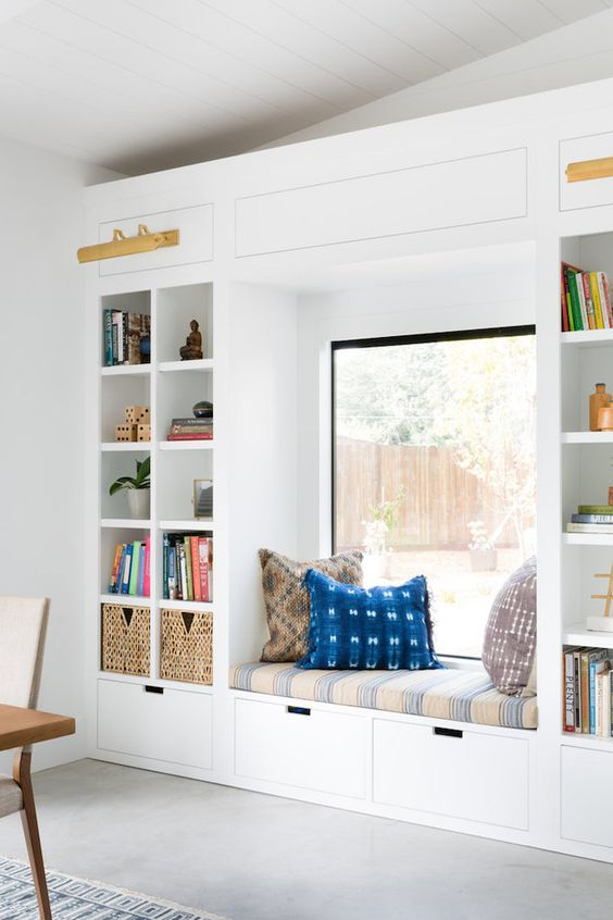a contemporary windowsill reading nook with an upholstered bench, drawers and shelves for storage plus bright pillows
