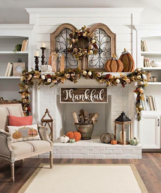a cool Thanksgiving mantel with faux pumpkins, leaves and wooden pumpkins, firewood, crochet pumpkins and candles