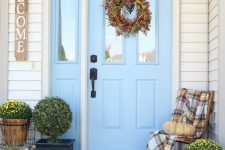 a cool Thanksgiving porch with a fall wreath, potted blooms and greenery and natural pumpkins is lovely