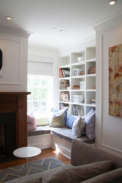 a corner windowsill reading nook with built-in shelves and colorful pillows is super cozy