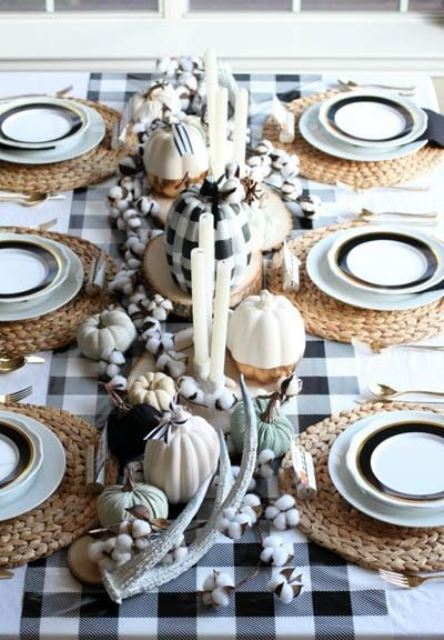 a cozy Thanksgiving centerpiece of white, plaid, color block pumpkins, antlers, cotton and candles is very chic