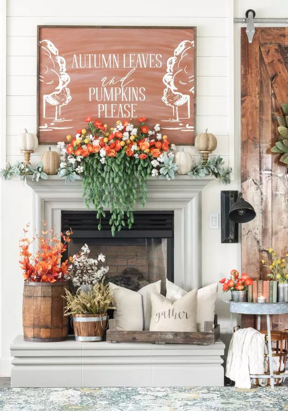 a cozy Thanksgiving mantel with lush greenery and blooms, faux pumpkins, an oversized sign and cotton and leaves in a basket