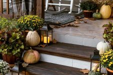 a cozy Thanksgiving porch with fall leaves, candle lanterns, pumpkins and gourds and bright potted blooms