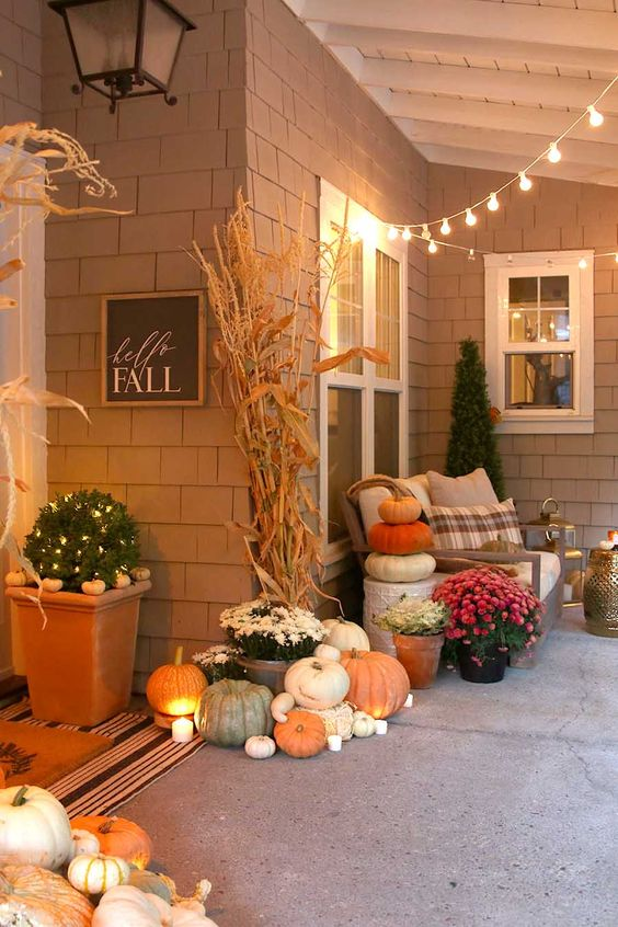 a cozy Thanksgiving porch with lots of pumpkins stacked, candles, corn husks and potted blooms