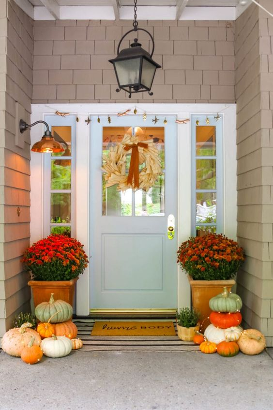 a cozy and colorful Thanksgiving porch with potted blooms, potted greenery, a corn husk wreath and stacked pumpkins with lights