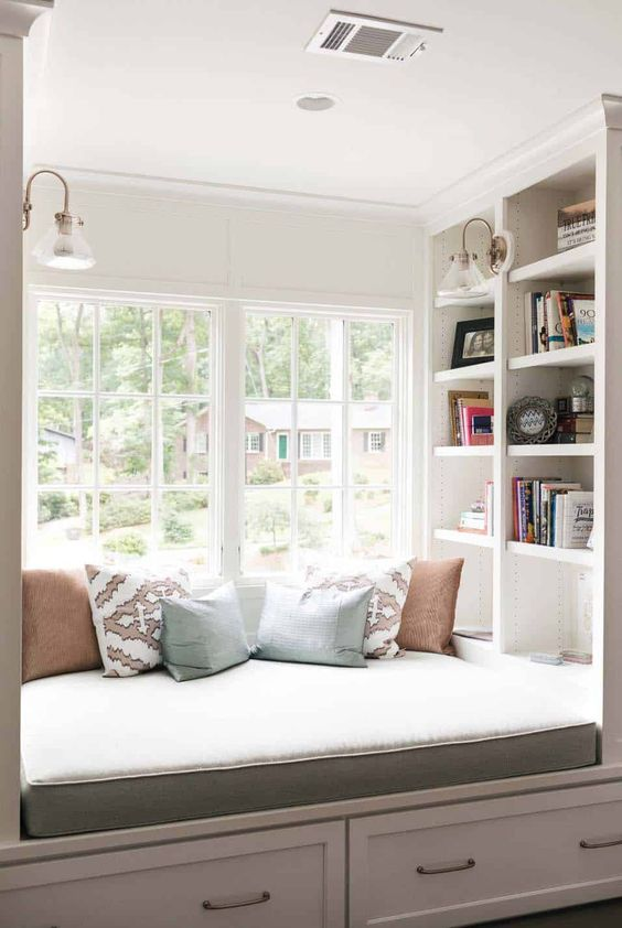 a cozy reading nook by the window - an upholstered bench with pillows and some shelves built in here and there