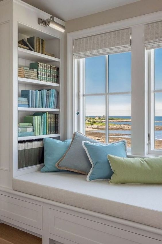 a cozy windowsill reading nook with an upholstered bench, colorful pillows and built in bookshelves on each side of the bench