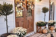 a farmhouse Thanksgiving porch with white potted blooms, heirloom pumpkins, wreaths of burlap and pinecones