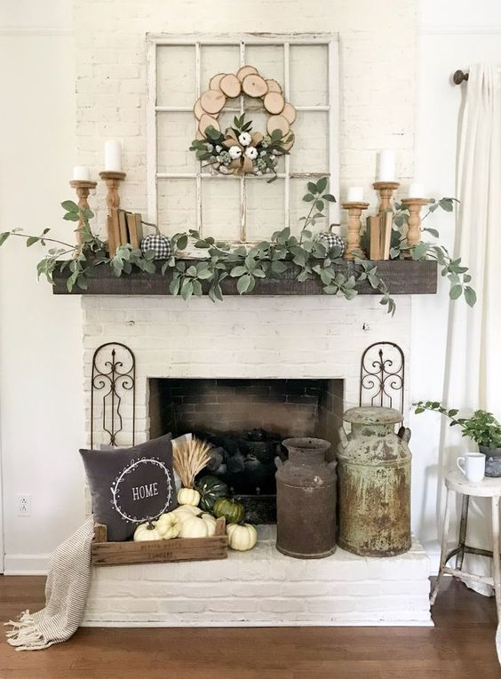 a farmhouse mantel with greenery, candles in wooden candleholders, faux pumpkins, a wood slice wreath with pumpkins and pumpkins by the fireplace