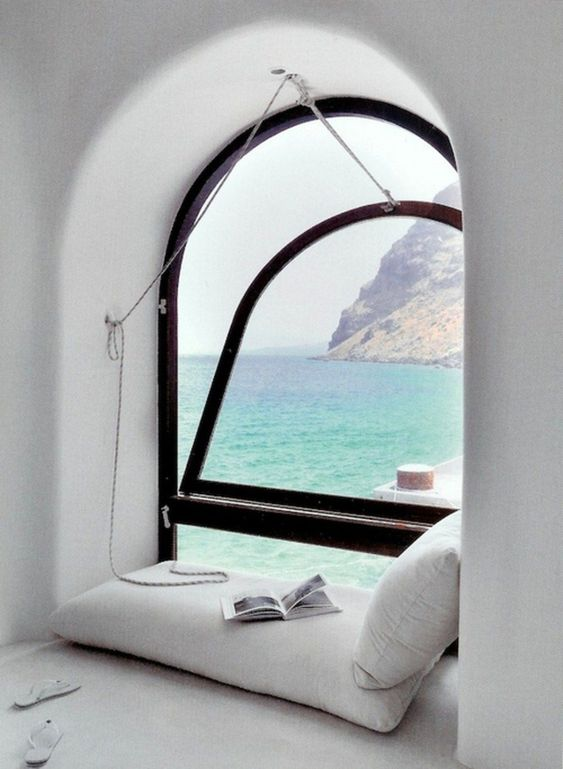 a gorgeous reading nook with a mattress and pillows by a pivot arched window with a gorgeous sea views just wows