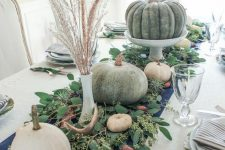 a harvest Thanskgiving centerpiece of fresh eucalyptus, antlers, white and green pumpkins and wheat in vases
