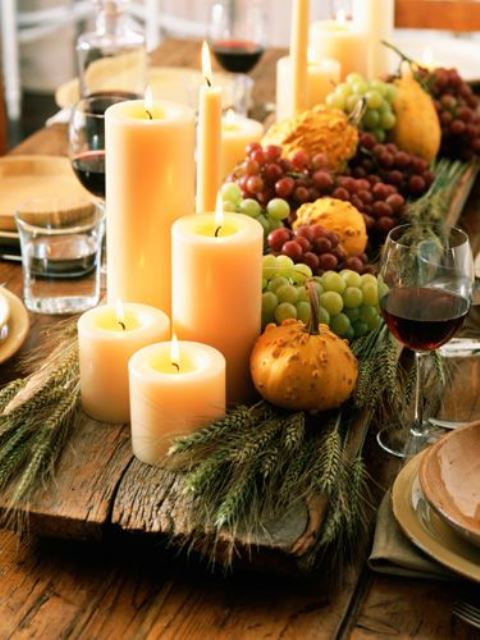 a harvest centerpiece of a wooden board, wheat, grapes, gourds, candles is a beautiful Thanksgiving piece