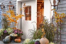 a harvest porch with usual and heirloom pumpkins, candle lanterns, bold leafy branches and grass is veyr natural