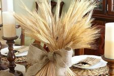 a large bundle of wheat with a giant burlap bow and large acorns and candles make up a chic Thanksgiving centerpiece