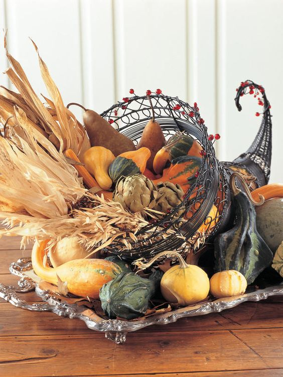 a metal cornucopia centerpiece with vegetables, corn husks and wheat inside will last long if you take faux veggies