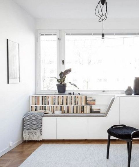 a minimalist windowsill reading space with a comfy bench, blankets and some bookshelves built-in here