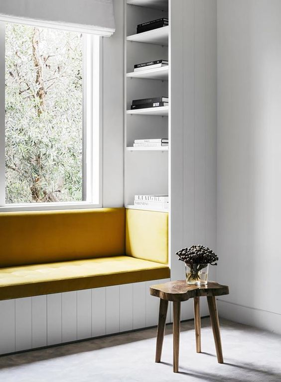a minimalist windowsill reading space with a leather upholstered bench and built-in bookshelves on each side of it