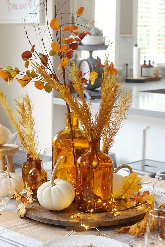 a modern Thanksgiving centerpiece of a wooden tray with lights, fall leaves, white pumpkins, dried leaves and grasses