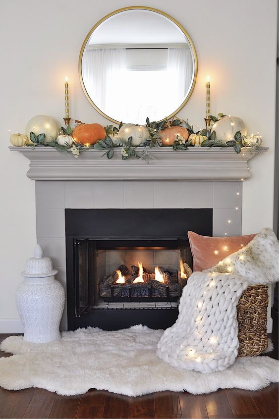 a modern Thanksgiving mantel with large pumpkinsm leaves, candles and lights is a very chic idea