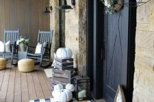 a monochromatic Thanksgiving porch with white pumpkins, candle lanterns, monochromatic textiles and a cotton wreath