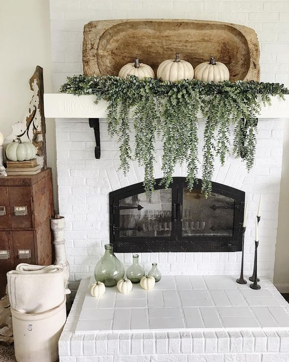 a natural Thanksgiving mantel with fresh cascading greenery, white pumpkins and a white bread bowl