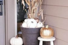 a neutral Thanksgiving porch with white pumpkins, a candle lantern, corn husks and gold pumpkins is elegant