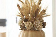 a cute pumpkin centerpiece with faux flowers