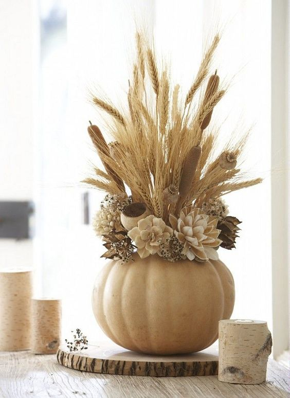 a neutral carved pumpkin vase with faux flowers, wheat and berries is very chic and peaceful decoration