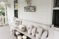 a neutral fall porch with a white bench with natural pumpkins, neutral pillows and prints