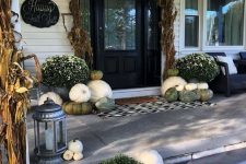 a neutral fall porch with white and green pumpkins and gourds, a printed rug, white blooms in pots