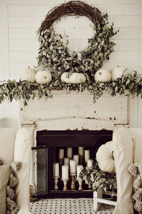 a neutral rustic mantel with greenery and white pumpkins, a vine wreath with leaves and candles in the fireplace