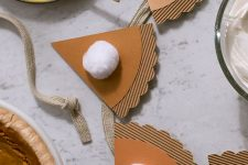 a pumpkin pie garland of cardboard and white pompoms is always a stylish and cute decor idea for Thanksgiving