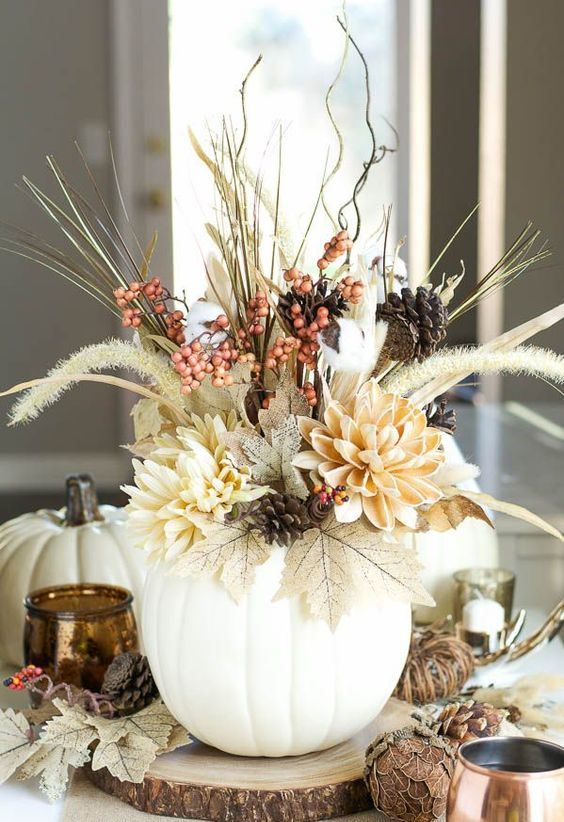 a rustic Thanksgiving centerpiece of a white pumpkin, dried leaves, blooms, berries, grasses and pinecones