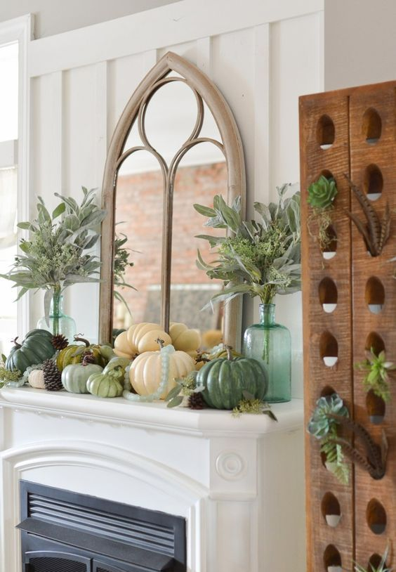 a rustic Thanksgiving mantel with various pumpkins, pinecones, greenery in bottles and leaves