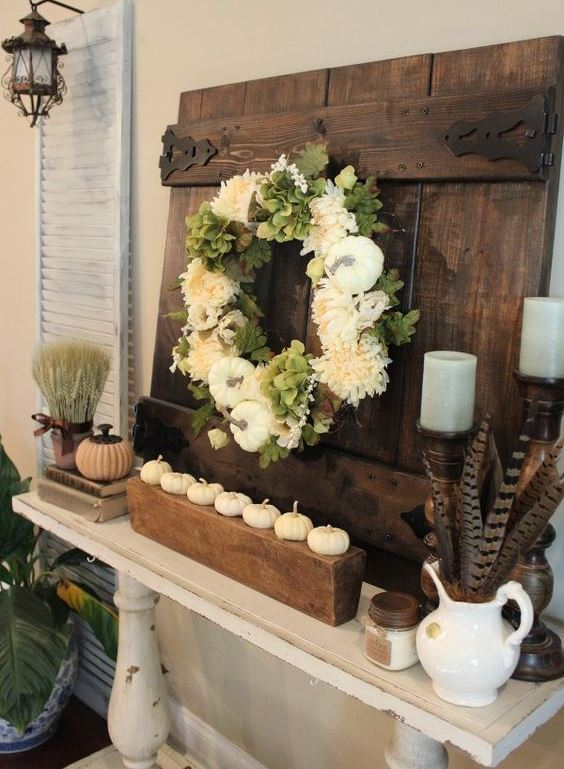 a rustic Thanksgiving mantel with white pumpkins on a stand, a white flower and pumpkin wreath, grey candles, feathers and a wheat bundle