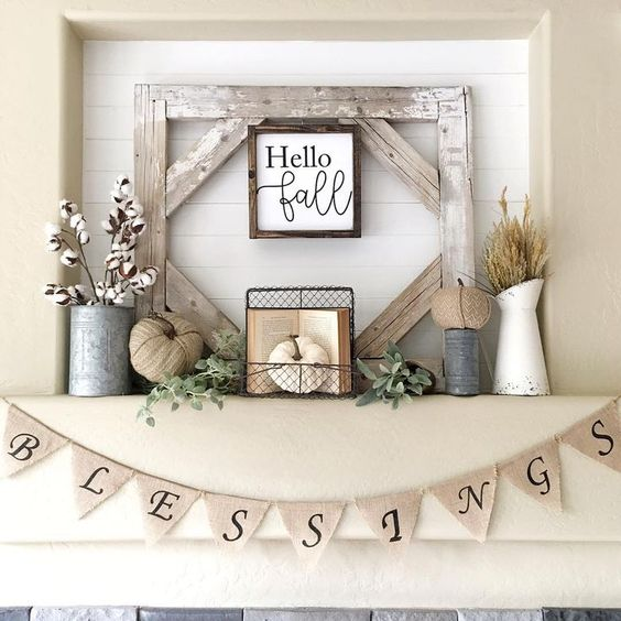 a rustic fall or Thanksgiving mantel with cotton, fabric pumpkins, herbs and a sign in a frame