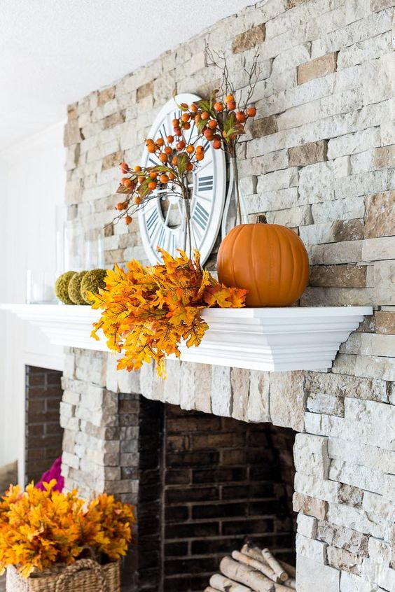 a rustic mantel with fall leaves, moss balls, pumpkins and fruits on the branches is suitable for both fall and Thanksgiving
