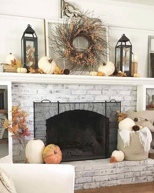 a rustic mantel with faux leaves and pumpkins, a vine wreath with leaves and candles with leaves for Thanksgiving