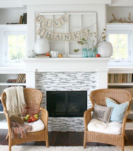 a simple Thanksgiving mantel with white and colorful pumpkins, branches with leaves and banners is a cool idea